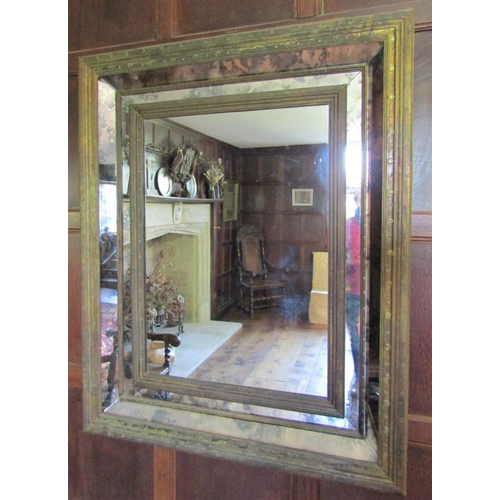 137 - A contemporary wall mirror in an antique style, the deep moulded frame with further mirror panel ins...