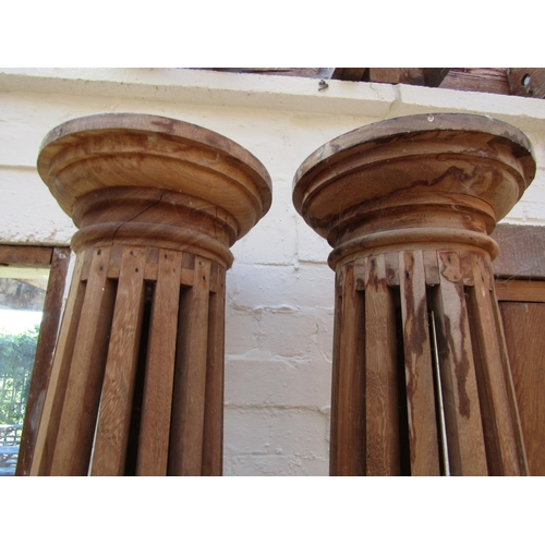 192 - A pair of teak wood columns of cylindrical tapering form with hollow centres, raised on square cut b...