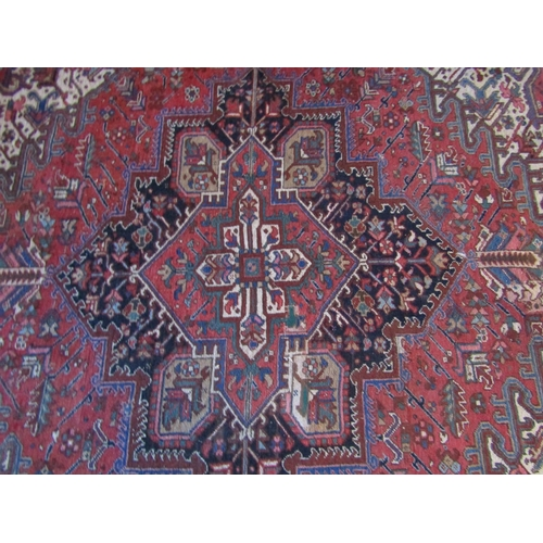 215 - An old eastern wool carpet, the central lozenge shaped medallion upon a red field with abstract foli...