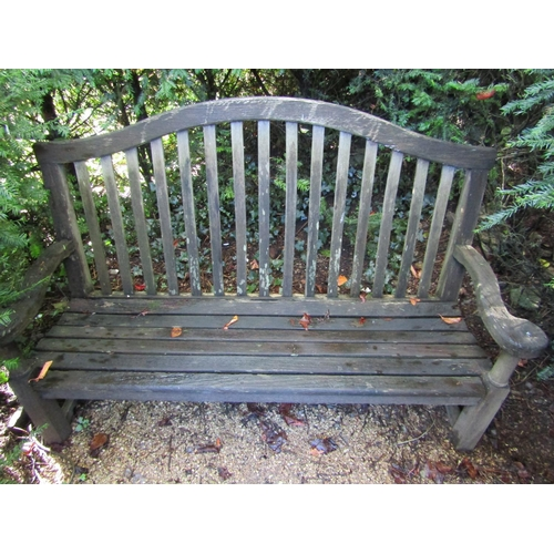 26 - A weathered teak wood garden bench, with scrolled arms and slatted back, 100cm wide