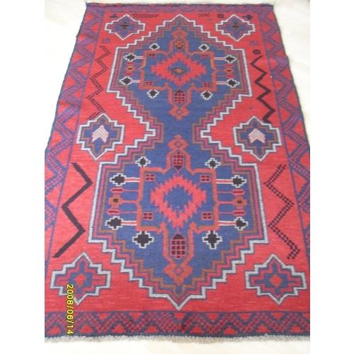 An Afgan hand-knotted herathi balouchi burgundy-ground wool rug with multicoloured isometric decoration with single border and short fringe, 111 x 188 cm