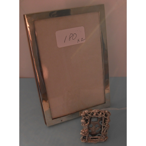 A George V rectangular silver photo frame with wooden easel support, Birmingham 1917, 15.5 x 10 cm and a Continental white metal miniature photo frame with carved figures on easel, 5 x 3.5 cm (2)