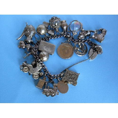269 - A 9ct gold charm bracelet to include a 1904 gold sovereign and two 18ct charms. Gross weight: 132g...