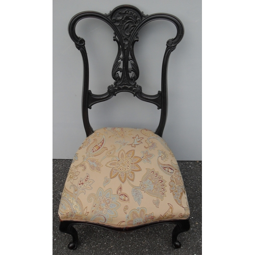 18 - A Victorian lacquered low-sized occasional chair with elaborate carving to top rail and fret work to...