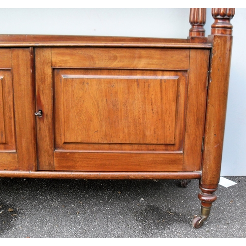 16 - A George IV mahogany buffet or dumb waiter with raised back, moulded top, fluted column supports, tw...