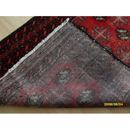 18 - A Persian hand-knotted Turkman-style burgundy-ground wool runner with contrasting multicoloured moti...