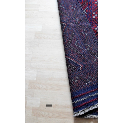 23 - An Afghan hand-knotted burgundy-ground Meshwani wool runner with short fringe, 60 x 249 cm in good c...