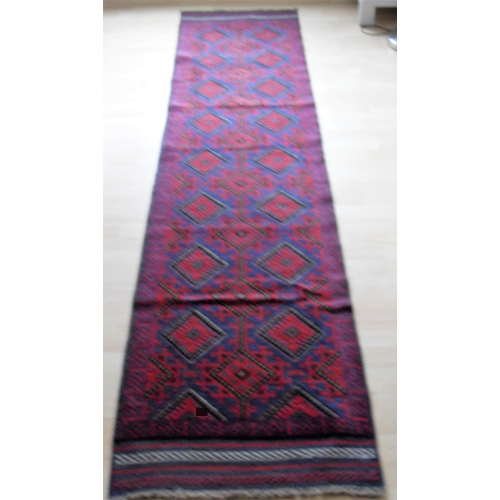 34 - An Afghan hand-knotted Meshwani blue-ground wool runner with multi-coloured lozenge designs, single ...
