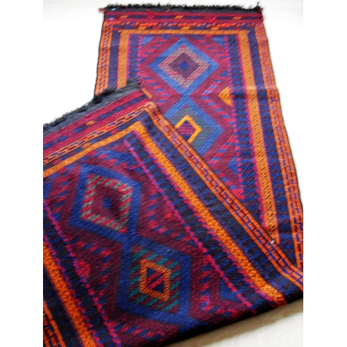33 - A hand-knotted Afghan Suzani blue-ground wool runner with bright multi-coloured zigzag designs, doub...