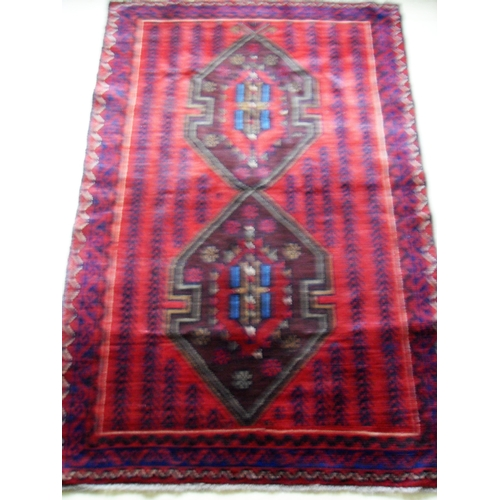 32 - An Afghan hand-knotted burgundy-ground Herathi Balochi wool rug with multi-coloured designs, single ...