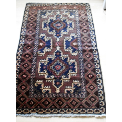 27 - An Afghan hand-knotted maroon-ground Herathi Balochi wool rug with isometric designs, double border ...