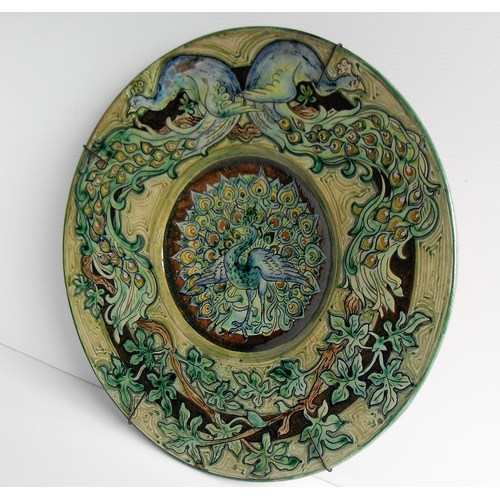 128 - An Art Nouveau Della Robbia earthenware green-ground charger with stylized sgrafitto peacock designs...