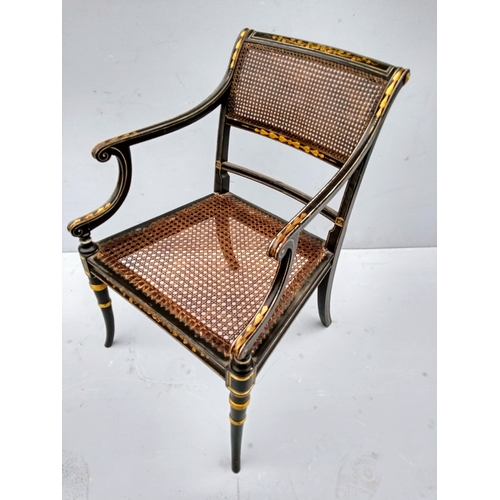 14 - A set of four Regency lacquered and parcel gilt carvers with rattan supports and seats on sabre legs...