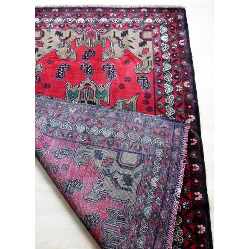 24 - An Afghan hand-knotted Herathi Balochi burgundy-ground wool rug, single border with short fringe, 95...