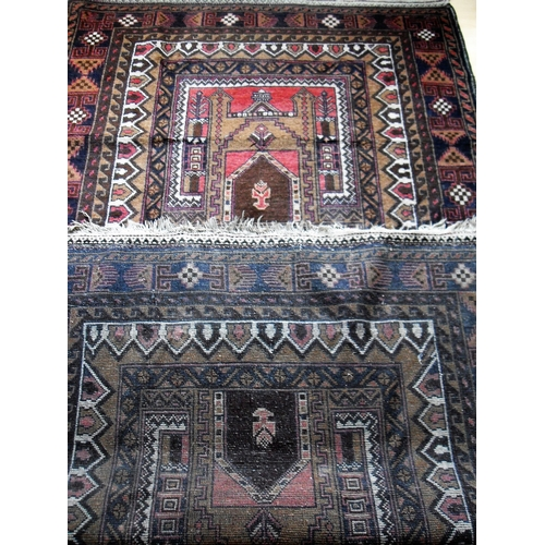 30 - An Afghan hand-knotted Herathi Balochi maroon-ground wool rug with multi-coloured designs, double bo...