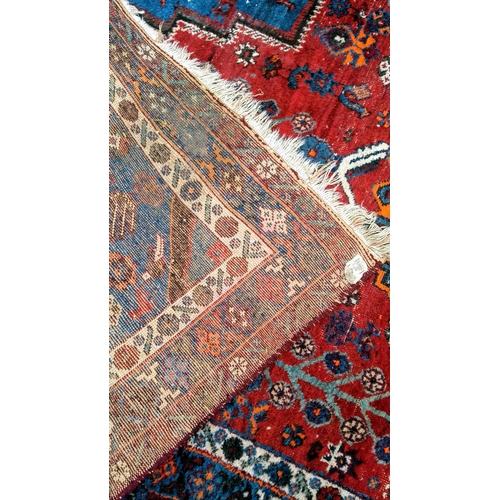 25 - An Oriental blue-ground hand-knotted rug with multi-coloured isometric designs, double border and me...