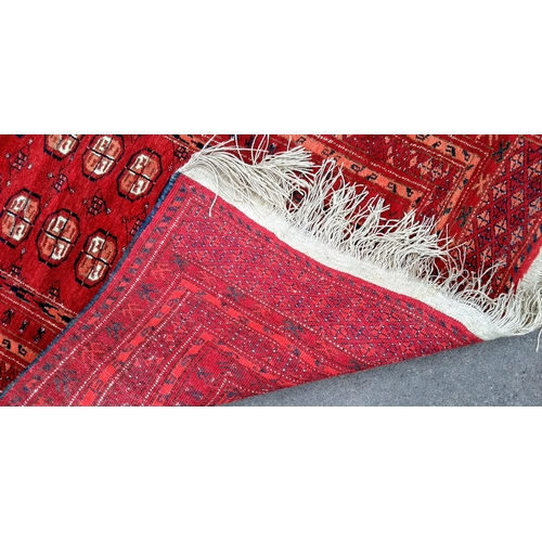 24 - An Oriental burgundy-ground hand-knotted bokhara runner with triple border and long fringe, 240 x 10...