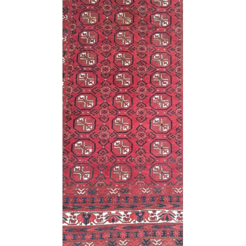 23 - An Oriental burgundy-ground hand-knotted bokhara rug with double border and long fringe, 210 x 132 c...