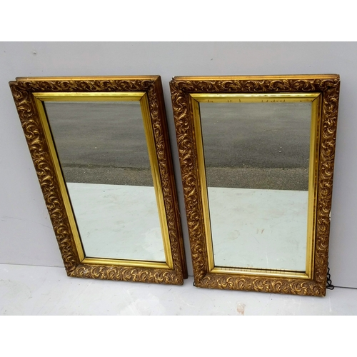 22 - A pair of oblong mirrors in profusely carved gilt frames, each 82 x 50 cm...