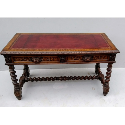 16 - A Victorian Gothic Revival oak writing table with elaborate carving, leather inset, twin frieze draw...