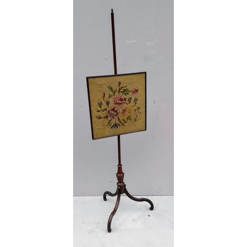 15 - An early 19th century mahogany-framed pole screen with pineapple finial, embroidered screen on a tri...