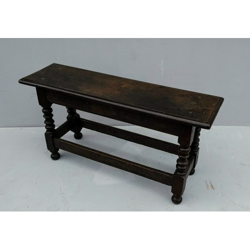 8 - An 18th century oak long joint stool with bobbin and stretcher supports, 49 x 95 x 26 cm...
