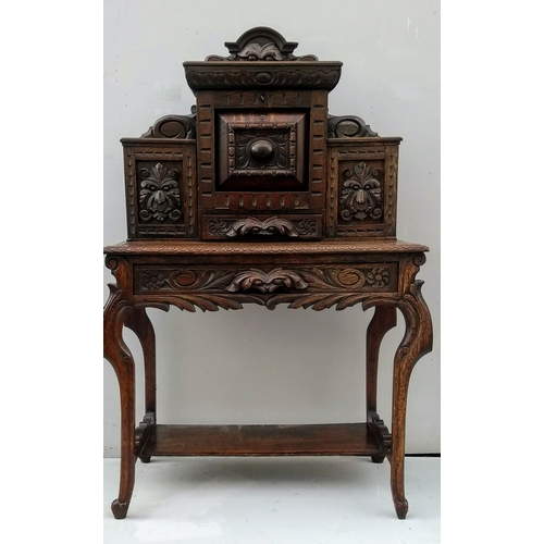 6 - A 19th century oak bonheur du jour with elaborate carved foliate decoration, enclosed compartments, ...