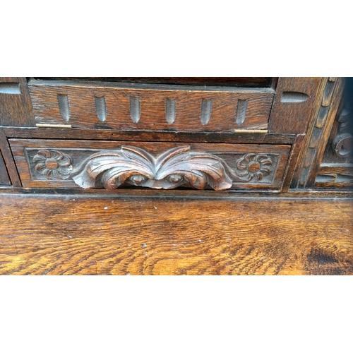 6 - A 19th century oak bonheur du jour with elaborate carved foliate decoration, enclosed compartments, ...