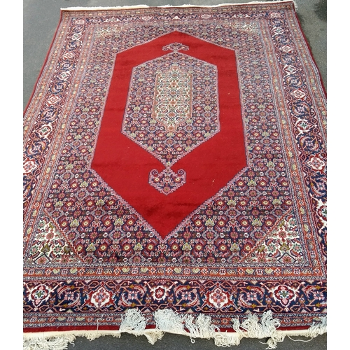31 - An Oriental hand-knotted multi coloured burgundy-ground wool rug with double border and long fringe,...