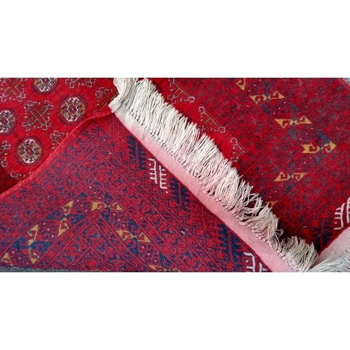36 - A burgundy-ground hand-knotted Baluch rug with single border and long fringe, in very good condition...