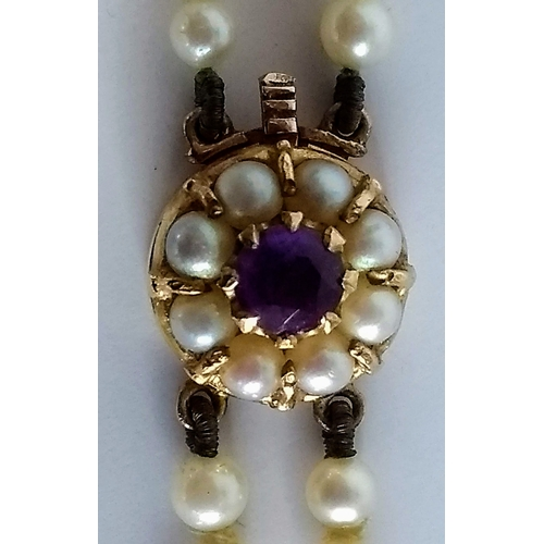 251 - A double string of cultured pearls with an amethyst mounted on a gold clasp, stamped 9ct, 47 cm...