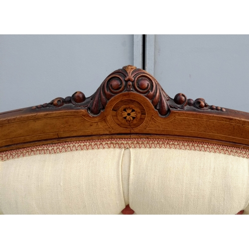13 - A Victorian walnut-framed sofa with arched support, string inlay and marquetry decoration, button ba...