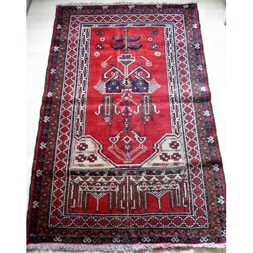 19 - An Afghan hand-knotted burgundy-ground Balochi wool rug with multi-coloured isometric designs, doubl...
