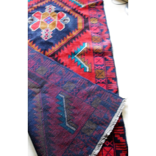 20 - An Afghan wool Hearthi Balochi burgundy-ground hand knotted rug with multicoloured isometric designs...