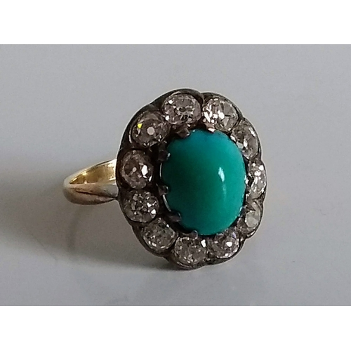265 - A turquoise and diamond cluster ring in a white and yellow metal setting, size K, oval cabochon 10mm...