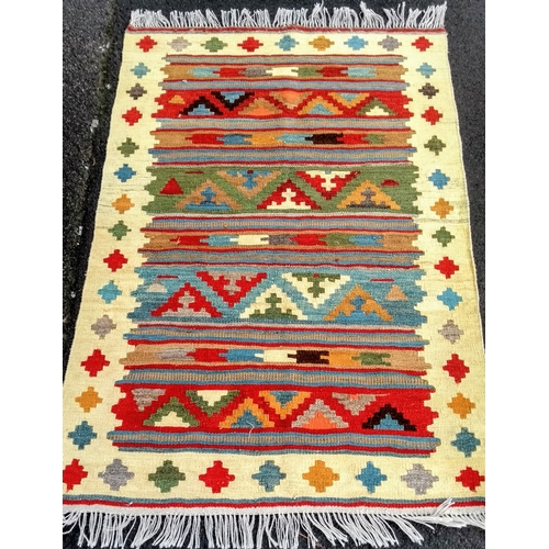 25 - An ivory-ground Turkish flat-weave wool kilim with multi-coloured isometric decoration and long frin...