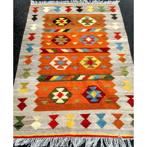 27 - An orange-ground Turkish flat-weave wool kilim with multi-coloured isometric decoration and long fri...