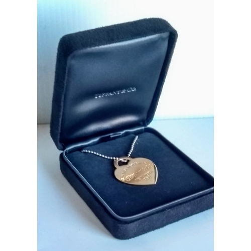 277 - A Tiffany & Co 18ct gold 'Please Return To' heart pendant, 15.08g on a Tiffany & Co .925 silver chai...