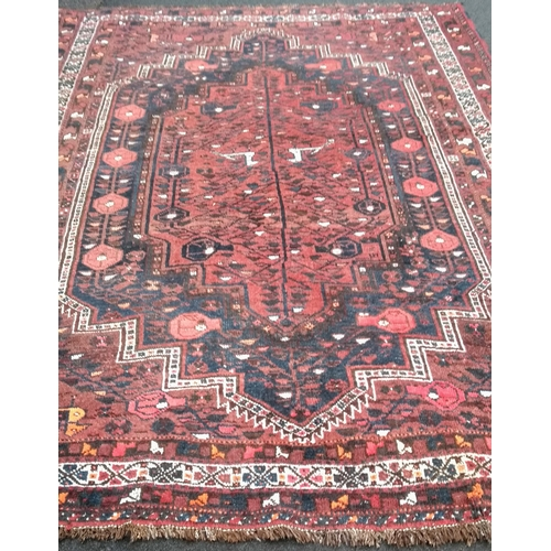 27A - An Oriental burgundy-ground hand-knotted drawing room wool rug with multi-coloured decoration, 300 x...