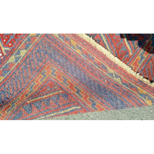 26 - An Afghan tribal hand-knotted burgundy Kazak wool rug with multi-coloured lozenge decoration, double...