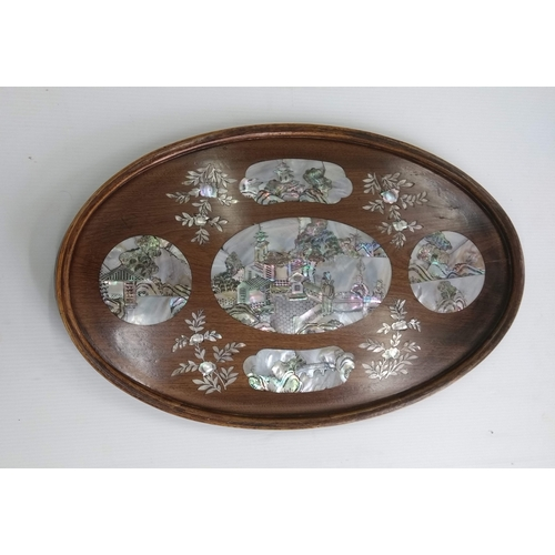 46 - An Oriental convex hardwood oval wall hanging with allegorical scenes with mother-of-pearl decoratio...