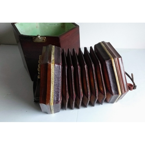 50 - An early 20th century twenty-button concertina with pierced decoration, leather-trimmed paper bellow...
