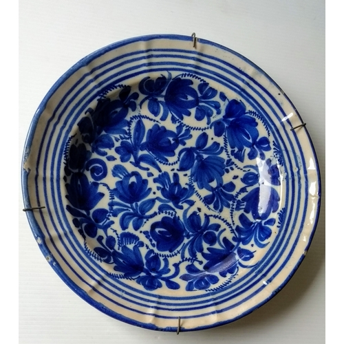 68 - Two 18th century blue and white delft tin plate circular chargers with floral and foliate decoration...