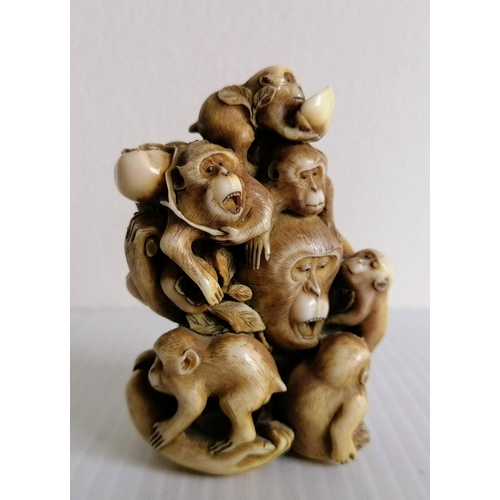 70 - A Japanese carved okimono of a group of monkeys, holding nuts and fruit, signed to base, 7.5cm H...