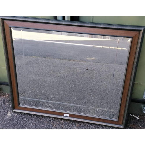 73 - An oblong wood-framed bevelled wall mirror, 75 x 90 cm...