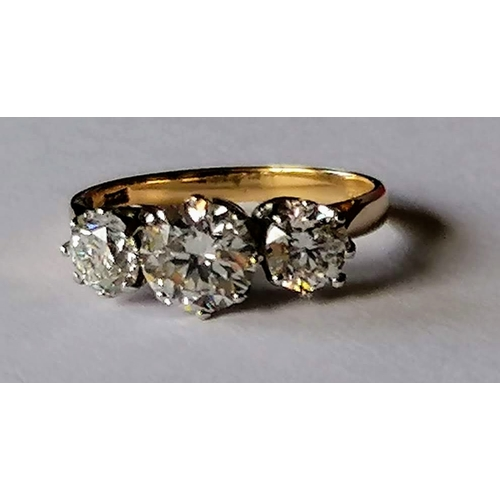 263 - A three-stone diamond ring on a 14ct yellow gold claw setting with three round brilliant-cut diamond...