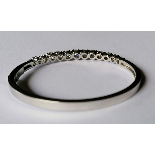272 - A diamond set oval hinged bangle comprising thirteen round brilliant-cut diamonds measuring from 4.1...