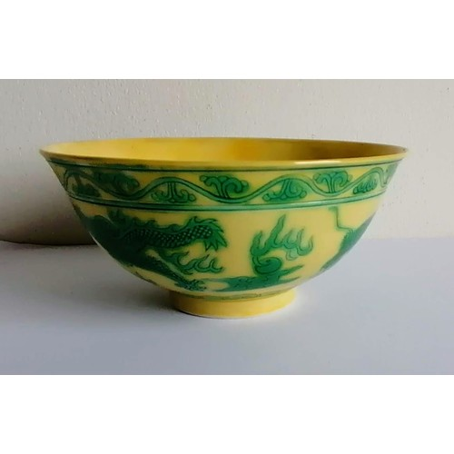 A green and yellow-glazed dragon bowl, incised and painted with a pair of five-claw dragons chasing flaming pearls between foliage and ruyi-head borders, the interior with shou characters, Guangxu six-character marks to base and of the period, 13.8 cm diameter. Condition: the rim had been repaired
