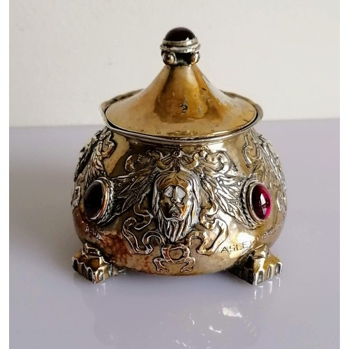 109 - An Arts and Crafts silver pot and cover of circular tapering form, embossed with grotesque masks, ri...