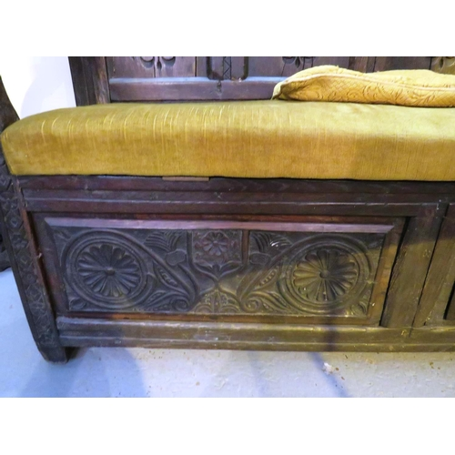 17 - ANTIQUE CARVED STORAGE SEAT SETTLE WITH GREEN VELOUR CUSHIIONED SEAT...